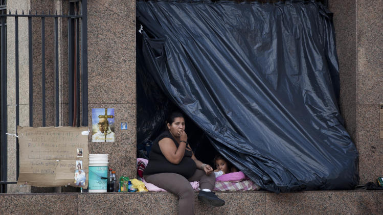In this May 14, 2013 photo, a homeless woman sits next to her plastic tarp, along with a child, at the building where Pope Francis used to live when he was archbishop, near the Metropolitan Cathedral, in Buenos Aires, Argentina. With an Argentine on the throne of St. Peter, the South American country's capital city has launched a series of guided tours. Three-hour weekend bus trips and walking tours are so far non-commercial in the first step at papal tourism. The bus tours wind through Buenos Aires twice each Saturday and Sunday and can carry about 40 passengers, cruising past 24 sites linked to the new pope. There's no charge for the trip, or for more limited walking tours of downtown and neighborhood sites Tuesdays and Thursdays. (AP Photo/Natacha Pisarenko)