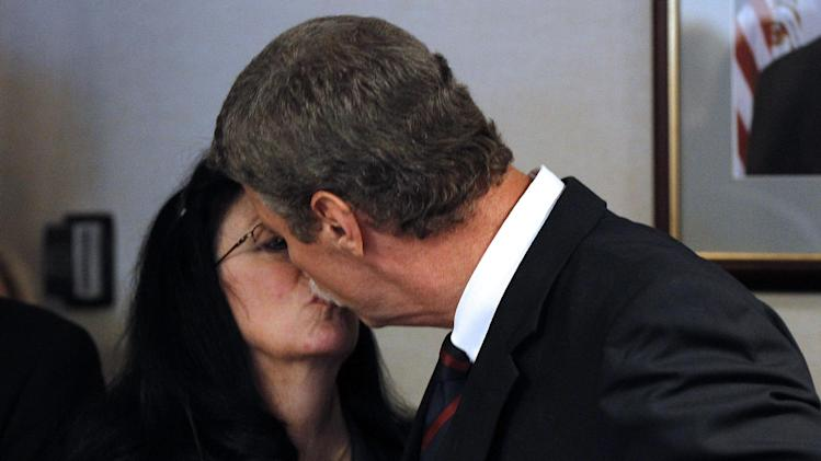 Jim Letten, U.S. Attorney for the Eastern District, kisses his wife JoAnn after announcing his resignation during a news conference in New Orleans, Thursday, Dec. 6, 2012.  Letten said his resignation is effective Dec. 11 and that he plans to stay on with the department briefly to help with the transition in leadership. (AP Photo/Gerald Herbert)