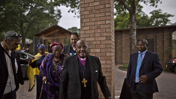 Retired Anglican Archbishop Desmond Tutu, center, arrives at the Nelson Mandela Centre of Memory in Johannesburg, South Africa, Monday, Dec. 9, 2013. Scores of heads of state and government and other foreign dignitaries, including royalty, are beginning to converge on South Africa as the final preparations for Tuesday's national memorial service for liberation struggle icon Nelson Mandela are put in place.(AP Photo/Muhammed Muheisen)