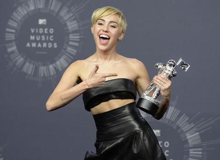 "Singer Miley Cyrus poses backstage after winning Video of the Year for ""Wrecking Ball"" during the 2014 MTV Video Music Awards in Inglewood"