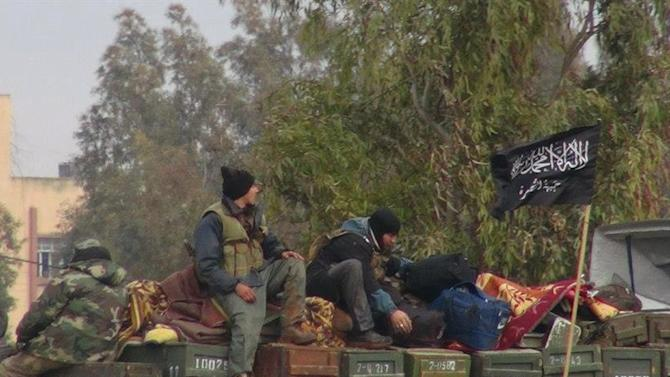 """This citizen journalism image provided by Edlib News Network, ENN, which has been authenticated based on its contents and other AP reporting, shows rebels from al-Qaida affiliated Jabhat al-Nusra, as they sit on a truck full of ammunition, at Taftanaz air base,  that was captured by the rebels, in Idlib province, northern Syria, Friday Jan. 11, 2013. Islamic militants seeking to topple President Bashar Assad took full control of a strategic northwestern air base Friday in a significant blow to government forces, seizing helicopters, tanks and multiple rocket launchers, activists said. The Arabic words on the flag, right, read:""""There is no God only God and Mohamad his prophet, Jabhat al-Nusra (their brigade name)"""". (AP Photo/Edlib News Network ENN)"""