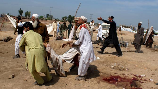 People carry an injured from a site of explosion at Jalozai camp on the outskirts of Peshawar, Pakistan, Thursday, March 21, 2013. A car packed with explosives blew up inside a refugee camp in northwestern Pakistan on Thursday as hundreds of people lined up to get food, killing and wounding dozens, police said. (AP Photo/Qazi Rauf)