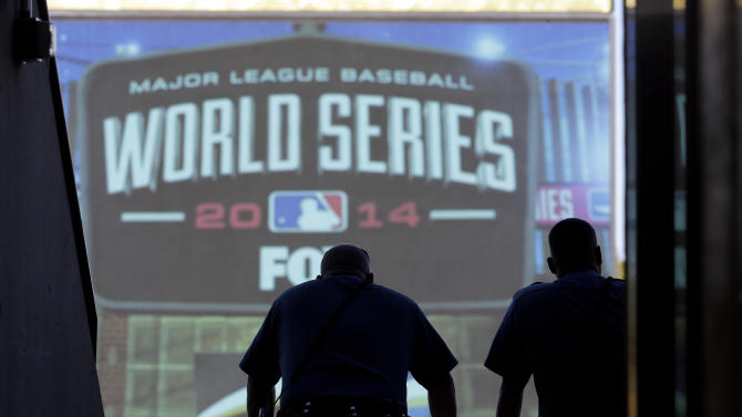 Some police officers look out over Kauffman Stadium before Game 1 of baseball's World Series between the Kansas City Royals and the San Francisco Giants Tuesday, Oct. 21, 2014, in Kansas City, Mo. (AP Photo/Charlie Riedel)