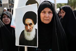 An Iraqi woman living in Iran holds a poster of the …