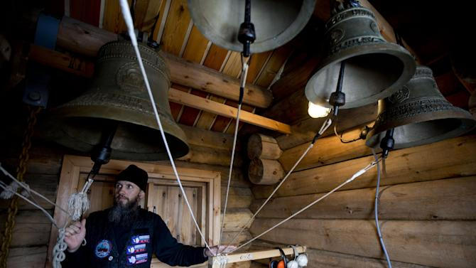 In this Feb. 1, 2015 photo, Russian Orthodox priest Sophrony Kirilov, 38, pulls on the strings of the heavy Russian bells inside the Holy Trinity Church on King George Island, Antarctica. The sound of bells inside the world's southernmost Eastern Orthodox church pierce the silence of the snow with a cacophonous and hypnotic sound similar to a railroad crossing. (AP Photo/Natacha Pisarenko)