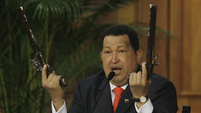 FOR USE AS DESIRED, YEAR END PHOTOS - FILE - In this July 24, 2012 file photo, Venezuela's President Hugo Chavez holds up a pair of pistols that he says belonged to Venezuela's independence hero Simon Bolivar during a ceremony marking 229th anniversary of Bolivar's birth at Miraflores presidential palace in Caracas, Venezuela.  Bolivar is the namesake of Chavez's Bolivarian Revolution movement, and his government is putting the finishing touches on a new mausoleum to house Bolivar's remains. (AP Photo/Fernando Llano, File)