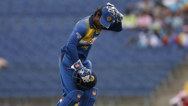 Sri Lanka's wicketkeeper Sangakkara swaps his helmet with his cap during their first ODI cricket match against Pakistan in Hambantota
