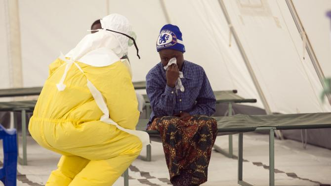 A health worker wearing protective gear attends to a newly admitted suspected Ebola patient in a quarantine zone at a Red Cross facility in the town of Koidu