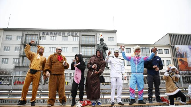 Carnival revellers stand in an empty tribune after Rosenmontag parade cancelled in Mainz
