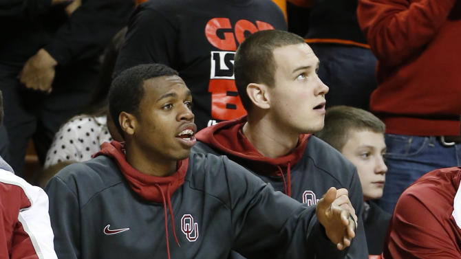 Oklahoma guard Buddy Hield gestures to a teammate as he sits on the bench with a boot on his injured right foot in the second half of an NCAA college basketball game against Oklahoma State in Stillwater, Okla., Saturday, Feb. 16, 2013. Oklahoma State won 84-79. (AP Photo/Sue Ogrocki)