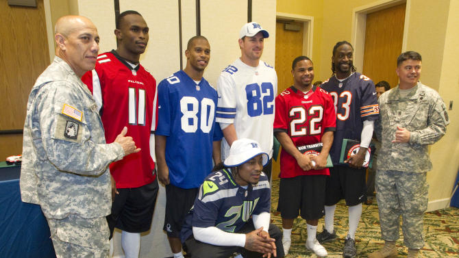 In this photo provided by IMG Consulting, Army Lt. Col. Stanley Garcia, far left, Atlanta Falcons wide receiver Julio Jones (11), New York Giants wide receiver Victor Cruz (80), Seattle Seahawks running back Marshawn Lynch (24), bottom, Dallas Cowboys tight end Jason Witten (82), Tampa Bay Buccaneers running back Doug Martin (22), Chicago Bears corner back Charles Tillman (33) and Commander Sgt. Maj. Joshua Amano, far right, pose for a picture at Schofield Barracks Thursday, Jan. 24, 2013, in Honolulu. The NFL football players met with members of the Warrior Transition Battalion and signed autographs then learned about how many of the United States Army soldiers where wounded in action at the USAA NFL sponsored event. (Eugene Tanner/AP Images for USAA. IMG Consulting