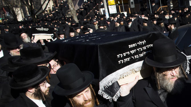 Members of the Satmar Orthodox Jewish community carry the coffins of two expectant parents who were killed in a car accident, Sunday, March 3, 2013, in the Brooklyn borough of New York. A  driver struck the car early Sunday morning, killing both parents while their baby, who was born prematurely, survived and is in critical condition. (AP Photo/John Minchillo)