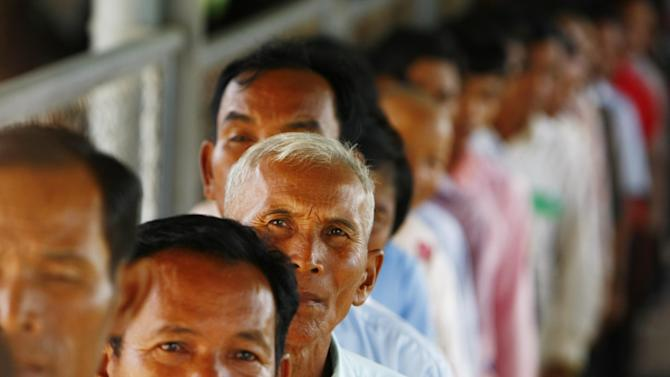 Cambodians line up at a court entrance before a hearing to prepare for the genocide trial of two surviving leaders Khieu Samphan and Noun Chea, at the U.N.-backed war crimes tribunal in Phnom Penh, Cambodia, Wednesday, July 30, 2014. (AP Photo/Heng Sinith)