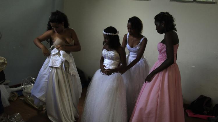 Fifteen-year-old girls help each other into their dresses as they prepare for a debutante ball in Rio de Janeiro
