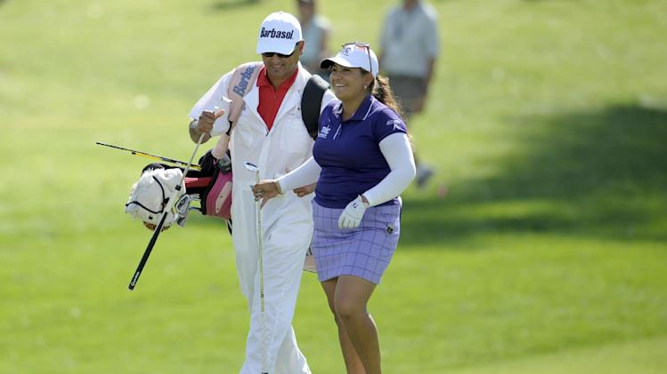 Lizette Salas, right, smiles after hitting a shot on the ninth hole during the third round of the LPGA Kraft Nabisco Championship golf tournament in Rancho Mirage, Calif., Saturday, April 6, 2013. At left is her caddie, Greg Puga. (AP Photo/Rodrigo Pena)