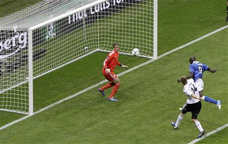 Italy's Balotelli scores a second goal against Germany's goalkeeper Neuer during their Euro 2012 semi-final soccer match at the National stadium in Warsaw