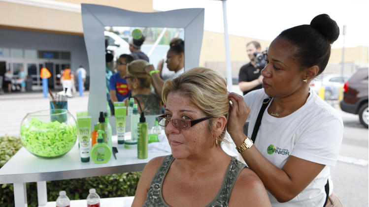 COMMERCIAL IMAGE -  A Garnier stylist styles a guests hair outside The Garnier Greener Tour Bus on Saturday June 16, 2012 in Houston. (Photo by Aaron M. Sprecher/Invision for Garnier/AP Images)