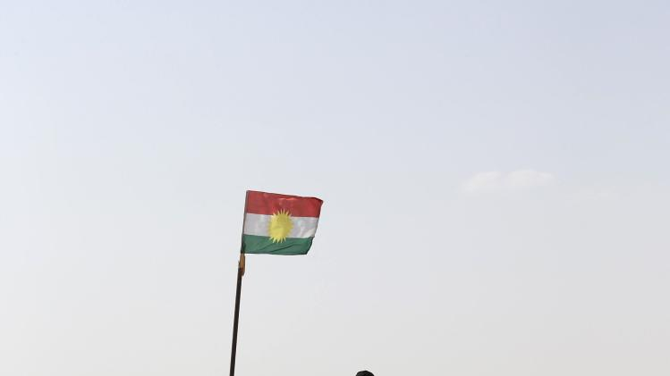Kurdish Peshmerga fighters keep watch on the Jalawla front line in the northeastern district of Baquba near the city of Khanaqin