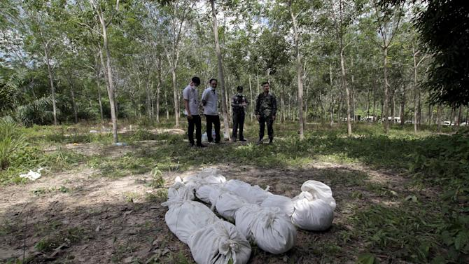 Policemen take notes behind human remains retrieved from a mass grave at a rubber plantation in Thailand's southern Songkhla province