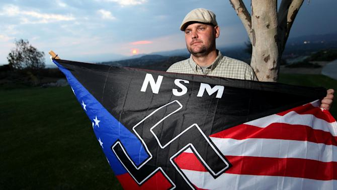 FILE - In this Oct. 22, 2010 file photo, Jeff Hall holds a Neo Nazi flag while standing at Sycamore Highlands Park near his home in Riverside, Calif. On Tuesday, Oct. 30, 2012, the trial begins in juvenile court for the 10-year-old boy charged with murder for shooting Hall, his white supremacist father while he slept on the couch in 2010. The child told investigators he killed his father with a gun kept unlocked in the family's home because he was tired of his father beating him and his stepmother. (AP Photo/Sandy Huffaker, File)