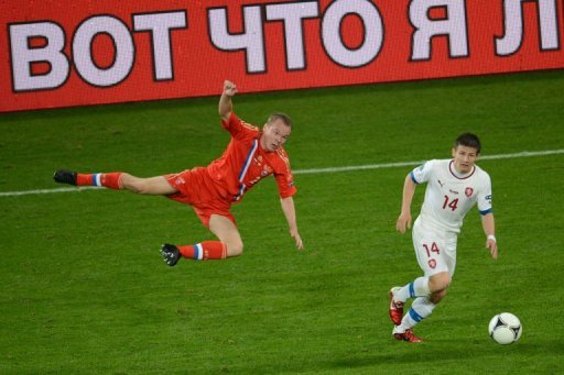Russian defender Aleksander Anyukov (L) goes airborne next to Czech midfielder Vaclav Pilar