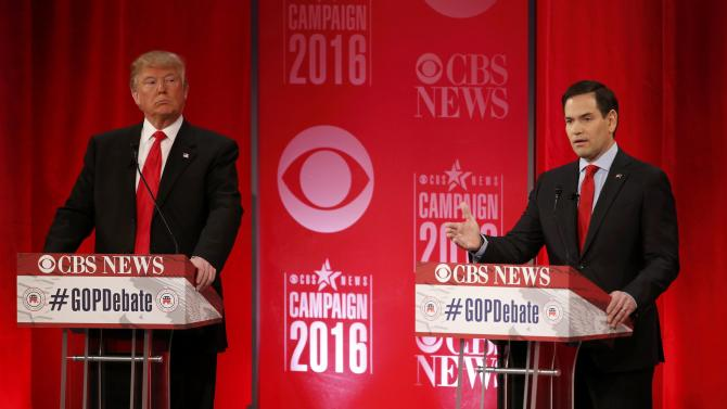 Republican U.S. presidential candidate Trump listens as Rubio speaks at the Republican U.S. presidential candidates debate sponsored by CBS News and the Republican National Committee in Greenville