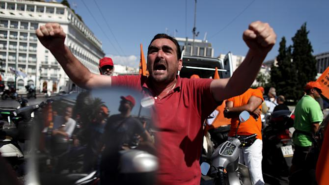 A municipal worker shouts slogans during a protest against the new austerity measures outside the Parliament in Athens, on Wednesday, Oct. 3, 2012. The country's budget includes about euros 7.8 billion worth of austerity measures for next year. They are part of a euro13.5 billion package of spending cuts and tax hikes for 2013 and 2014 that Greece's international creditors have demanded in exchange for continued payout of the rescue loans that are protecting the country from a messy default. (AP Photo/Petros Giannakouris)