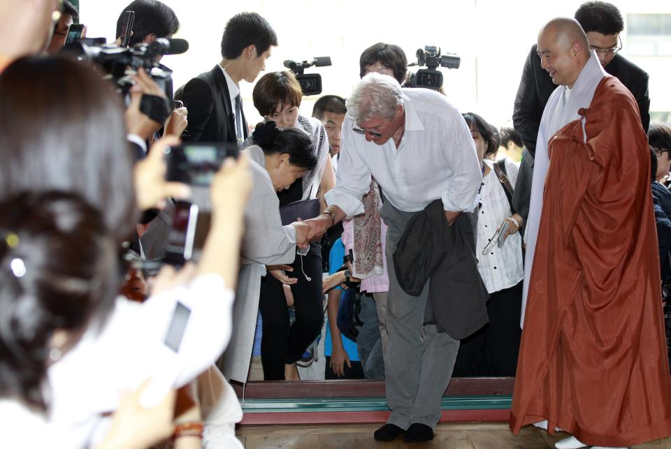 U.S. actor Richard Gere, center, greets with Buddhists during his visit to the Korean Buddhism's Chogye temple in Seoul, South Korea, Tuesday, June 21, 2011. Gere is in South Korea for six days to promote his photo exhibition and tour Buddhist temples. (AP Photo/ Lee Jin-man, Pool)