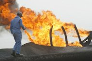 A man walks close to a flare at the North Rumaila oil field in southern Iraq. Iraq could more than double its current daily oil production by 2020, vastly boosting its economy and helping to bring stability to global energy markets, according to a forecast by the International Energy Agency