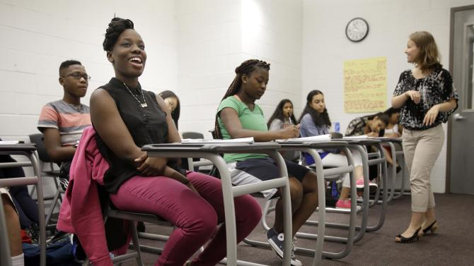 In this July 16, 2014 photo, Bintou Camara, 16, left, smiles during her English class at an Upward Bound program, which serves as a pathway to college for students from low-income families, in New York. That level of performance has earned Upward Bound strong bipartisan support in Congress, yet the national program nonetheless faces fiscal challenges because of the broader turmoil on Capitol Hill. (AP Photo/Seth Wenig)