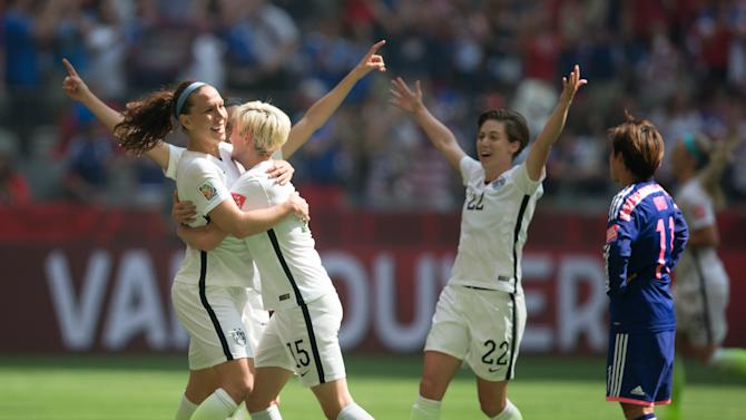United States' Lauren Holiday, left, Megan Rapinoe (15) and Meghan Klingenberg (22) celebrate Holiday's goal as Japan's Shinobu Ohno, right, watches during first half FIFA Women's World Cup soccer championship in Vancouver, British Columbia, Canada, Sunday, July 5, 2015.   (Darryl Dyck/The Canadian Press via AP) MANDATORY CREDIT