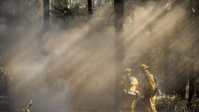 Firefighters check for hotspots while battling the King Fire near Fresh Pond, California