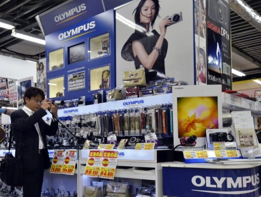 <p>File photo shows a man looking at a camera on an Olympus stand in a Tokyo camera shop. Olympus said Monday it had swung to a $100 million first-half profit, reversing a year-earlier loss, as the camera and medical equipment maker moves on from an embarrassing accounting scandal.</p>