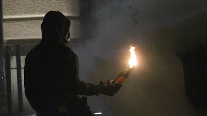 A protestor prepares to throw a petrol bomb to the nearby riot police near the parliament during clashes in Athens on Wednesday Nov. 7, 2012. Greece's fragile coalition government faces its toughest test so far when lawmakers vote later Wednesday on new painful austerity measures demanded to keep the country afloat, on the second day of a nationwide general strike. The euro13.5 billion ($17.3 billion) package is expected to scrape through Parliament, following a hasty one-day debate. But potential defections could severely weaken the conservative-led coalition formed in June with the intention of keeping Greece in the euro.(AP Photo Nikolas Giakoumidis)