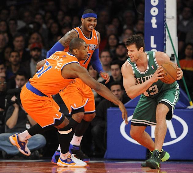 Boston Celtics' Kris Humphries (43) keeps the ball away from New York Knicks' Metta World Peace (51) and Carmelo Anthony (7) during the second half an NBA basketball game on Sunday, Dec. 8, 20