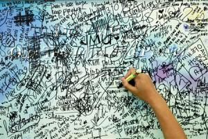 A man writes messages and well-wishes for family members…