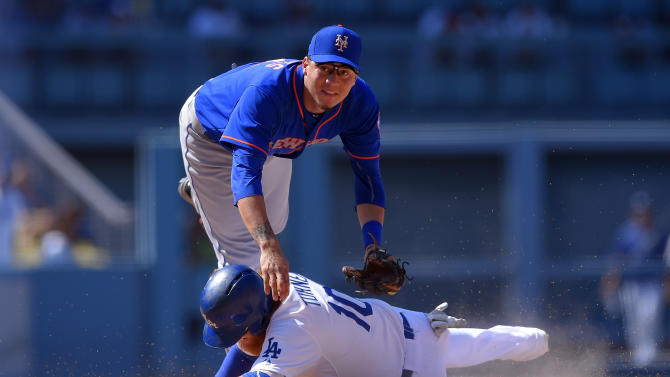 Los Angeles Dodgers' Justin Turner, below, is forced out at second as New York Mets second baseman Wilmer Flores attempts to throw out Alex Guerrero at first during the ninth inning of a baseball game, Sunday, July 5, 2015, in Los Angeles. Guerrero was safe at first on the play. (AP Photo/Mark J. Terrill)