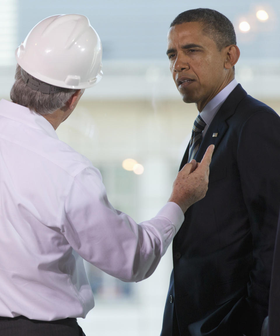President Barack Obama listens while touring a building under construction in Washington, Friday, Dec. 2, 2011, part of his Better Building Initiative to promote energy efficient buildings. (AP Photo/Carolyn Kaster)