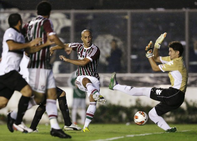 Euzebio of Fluminense challenges goalkeeper Silva of Olimpia during their Copa Libertadores soccer match in Rio de Janeiro