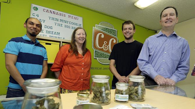 In this June 23, 2014 photo, Pete O'Neil, right, stands in his soon-to-be-open medical marijuana dispensary in Seattle with three of his employees. O'Neil struck out in Washington's lottery for coveted pot-shop licenses, and he has unsuccessfully tried to buy companies who did. In frustration, he's turning what would have been his Seattle retail store into a medical marijuana dispensary. Also pictured are Patricia Barker, second from left, grower representative, Adam Girton, second from right, product line advisor, and John Minehart managing director of U.S. Cannabis. (AP Photo/Ted S. Warren)