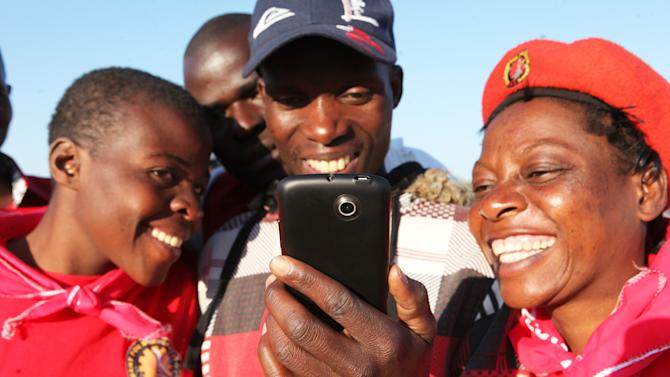 Zimbabweans enjoy accessing the internet to read about Baba Jukwa in Harare, Tuesday, July, 9, 2013. Baba Jukwa's name is whispered in buses, bars and on street corners by Zimbabweans eager for the inside scoop on President Robert Mugabe's ruling party. One avid follower even climbs a tree in a rural village for a signal to call a friend for the latest tidbits from the mysterious yet stupendously popular blogger. (AP Photo/Tsvangirayi Mukwzhi)