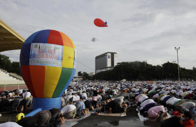 Filipino Muslims gather for an early morning prayer celebrating Eid al-Fitr, a Muslim holiday marking the end of Ramadan, the Islamic holy month of fasting, at the Quirino grandstand in Manila, Philip