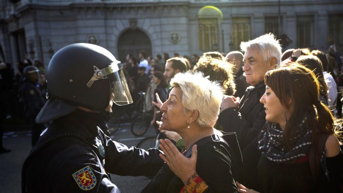 A riot police pushes a protestor during a general strike in Madrid, Spain, Wednesday, Nov. 14, 2012. Spain's General Workers' Union said the nationwide stoppage, the second this year, was being observed by nearly all workers in the automobile, energy, shipbuilding and constructions industries. (AP Photo/Daniel Ochoa de Olza)