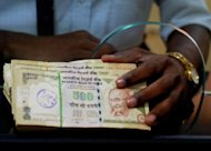 India's rupee hit a record low against the dollar Wednesday and stocks fell nearly two percent as uncertainty over the eurozone debt crisis and weak domestic indicators hit Asia's third-largest economy