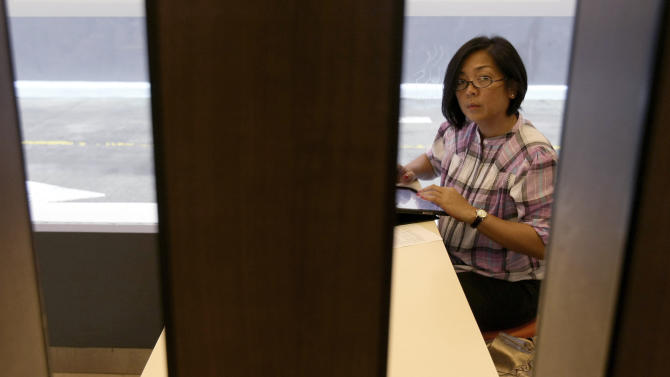 In this Tuesday, Aug. 16, 2011 photo, journalist Cookie Micaller, whose sister Cynthia Wilson was one of the victims in the 2001 terrorist attacks at the World Trade Center in New York, works on a story at an American fast food restaurant chain in Manila, Philippines. Micaller said she is frustrated by the resources the U.S. has spent fighting terrorism over the past decade, instead of combating disease, improving education and providing food and water to those in need. (AP Photo/Bullit Marquez)