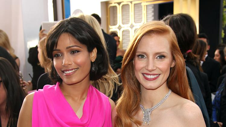 Actresses Freida Pinto, left, and Jessica Chastain arrive at the 19th Annual Screen Actors Guild Awards at the Shrine Auditorium in Los Angeles on Sunday, Jan. 27, 2013. (Photo by Matt Sayles/Invision/AP)