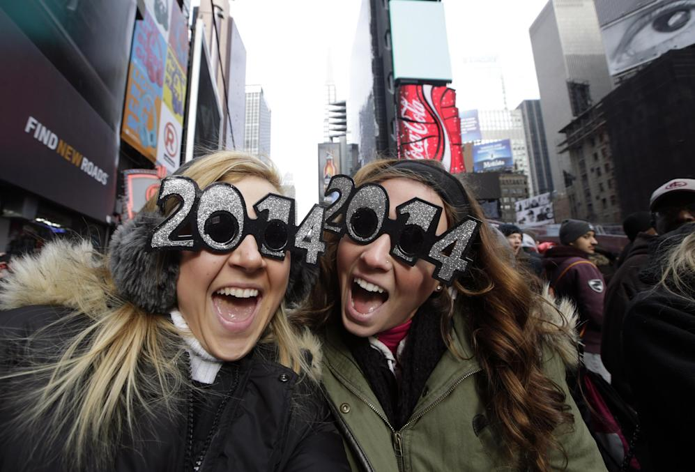 Veronica Boshen and Brittany Wells, of Allentown, Pa., pose for a photo with their 2014 glasses while waiting for the celebration to begin in Times Square on New Year's Eve, Tuesday, Dec. 31, 2013, in New York. (AP Photo/Kathy Willens)
