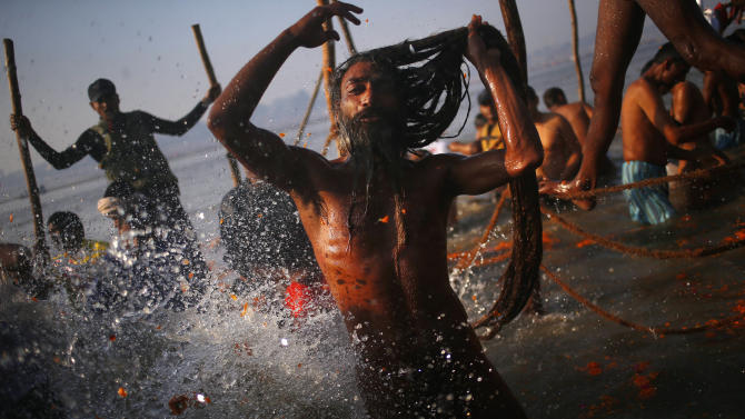 """A """"Naga"""" sadhu or Hindu naked holy man takes a dip at """"Sangam,"""" the confluence of Hindu holy rivers Ganges, Yamuna and the mythical Saraswati, during the Maha Kumbh festival at Allahabad, India, Sunday, Feb. 10, 2013. Millions of devout Hindus and thousands of Hindu holy men are expected to take a dip at Sangam on Sunday, the most auspicious day according to the alignment of stars, for the entire duration of Maha Kumbh festival, which lasts for 55 days. (AP Photo/ Saurabh Das)"""