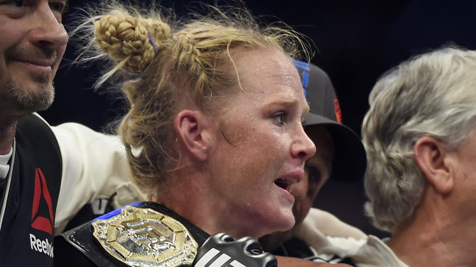 Holly Holm holds the champion belt after defeating Ronda Rousey during their UFC 193 bantamweight title fight in Melbourne, Australia, Sunday, Nov. 15, 2015. Holm pulled off a stunning upset victory over Rousey in the fight, knocking out the women's bantamweight champion in the second round with a powerful kick to the head Sunday. (AP Photo/Andy Brownbill)