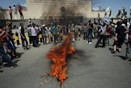 Yemeni protesters gather around fire during a demonstration outside the US embassy in Sanaa. Some protesters said they saw three vehicles being torched by some of the demonstrators after they gained access to the compound through an unguarded security gate